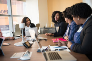 Women of color working around a conference table.