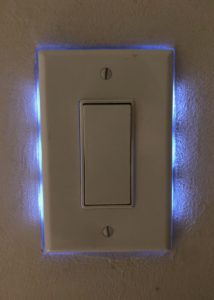 Wall paddle switch backlit with blue-white LED lights. It makes it glow from behind.