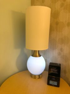 A table lamp. It has a tall cylindrical shade which covers a standard light bulb, and a large round base that glows like the moon.
