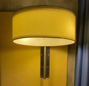 Cylindrical wall lamp with steel toggle switch under the shade. The switch is about the diameter of a ballpoint pen's ink barrel, and about the length of the first knuckle on your pinky finger.