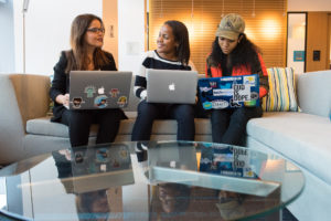 Three women on computers in a discussion.