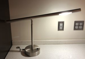 Brushed steel desk lamp with a flat steel base. A black rocker switch (about an inch long) is on the top of the base.
