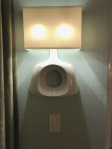 An odd wall lamp styled to look like someone had cut a table lamp in half and glued it to the wall, still working. The paddle switch is about 5 inches below it.