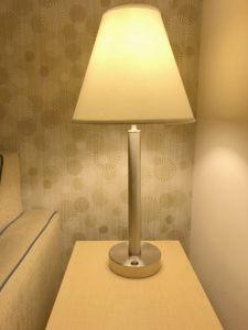 A brushed steel table lamp with a conical shade and a thin steel cylindrical body that ends at a thick cylindrical steel base and the same rocker switch as is on the desk lamp.
