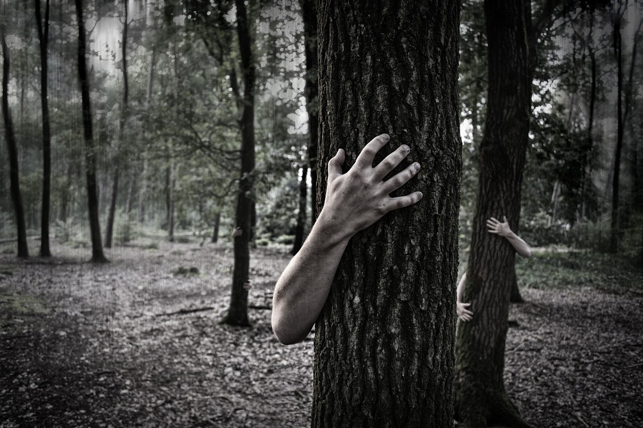 Zombie hands wrapping around tree trunks