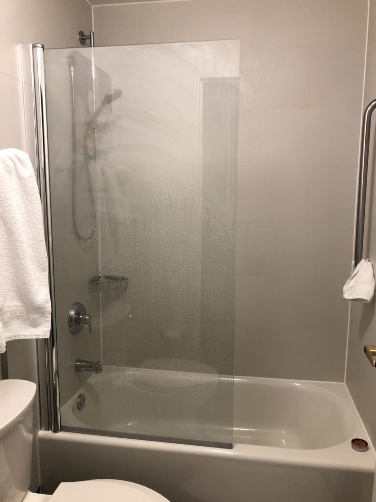 A hotel bathroom. From the door, the toilet is on the left. The tub is on the back wall behind the toilet. A glass panel covers half the shower area to ensure the toilet is not soaked. The shower controls can be seen (barely) through the wet glass.